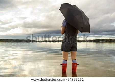 Woman holding an umbrella and standing in sea - stock photo