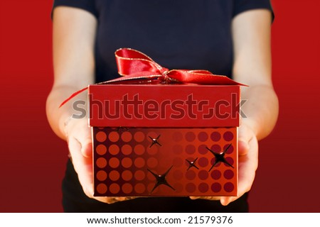 Woman holding and offering a gift to someone - stock photo