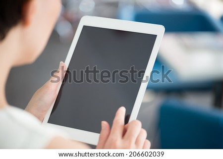 Woman holding and touching on a modern digital tablet and looking on a blank screen.  - stock photo