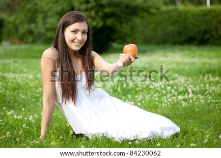 woman holding apple and sitting on the grass - stock photo