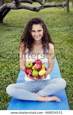 woman holding apple and sitting on the yoga-mat. Outdoor