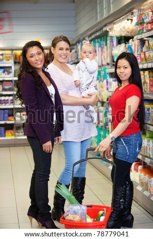 Woman holding baby and standing with friends while looking at camera