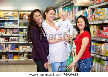 Woman holding baby and standing with friends while looking at camera in shopping centre