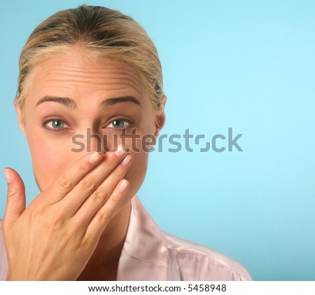 Woman holding back a sneeze with hand over nose - stock photo