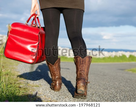 Woman holding bag and walking on road int he countryside