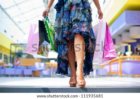 woman holding bags in shopping mall - stock photo