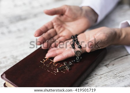 Woman holding balk rosary in her hands over bible