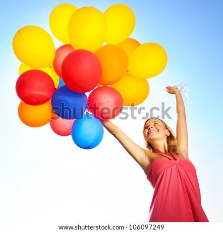 Woman holding balloons against sun and sky - stock photo