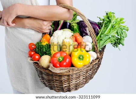 Woman holding basket of fresh organic vegetables from the farmers market  - stock photo