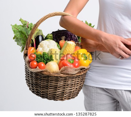 Woman holding basket of raw organic vegetables part of her household purchase, healthy living concept - stock photo