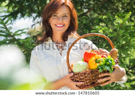 Woman holding basket of vegetables outdoors at her garden