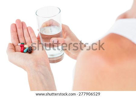 Woman holding batch of pills and glass of water on white background