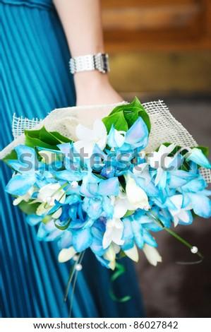 Woman holding beautiful azure wedding flowers bouquet - stock photo