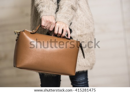 Woman holding beautiful small light brown leather bag