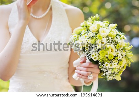 Woman holding beautiful wedding flowers bouquet - stock photo