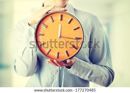 Woman holding big alarm clock, isolated on white background - stock photo