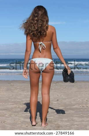 woman holding black flops on the shoreline - stock photo
