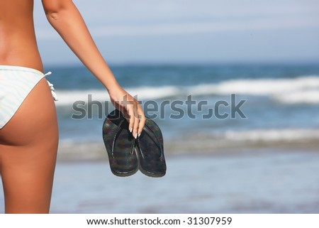 woman holding black flops on the shoreline