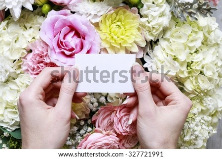 Woman holding blank paper card. Romantic flower ornament with rose, dahlia, hortensia and carnation flowers. - stock photo