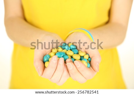 Woman holding blue-yellow candies - colors of flag of Ukraine, isolated on white - stock photo