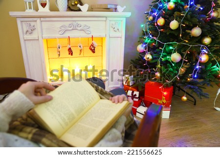 Woman holding book in front of fireplace - stock photo