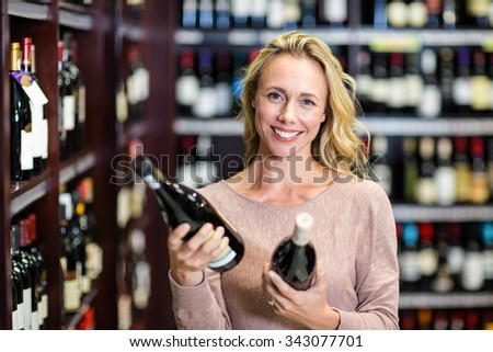 Woman holding bottles of wine in supermarket - stock photo