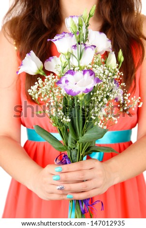 Woman holding bouquet of roses, on bright background, close-up