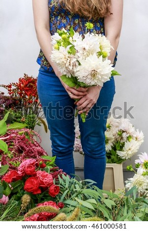 Woman holding bouquet of white dahlia flowers.