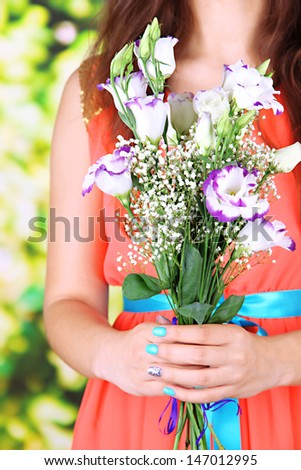 Woman holding bouquet, on bright background, close-up