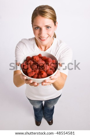 Woman holding bowl of raspberries - stock photo