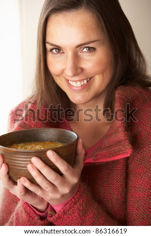 Woman holding bowl of soup - stock photo