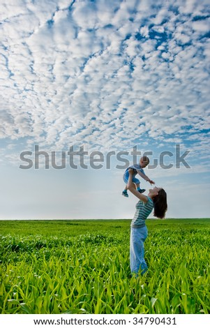 woman holding boy,  they standing on green field - stock photo