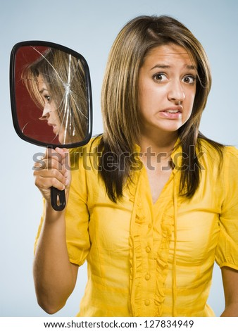 Woman holding broken hand held mirror - stock photo