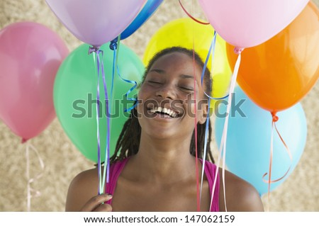 Woman holding bunch of balloons and laughing - stock photo