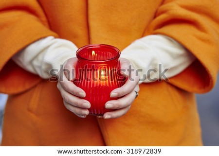 Woman holding burning candle in her hands. Christmas season holidays concept - stock photo