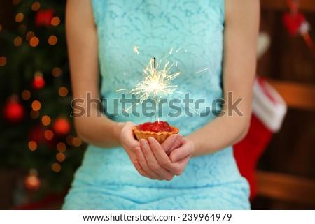 Woman holding cake with sparkler, on shiny background - stock photo