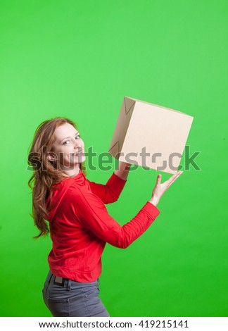 Woman holding cardboard box on green background - stock photo