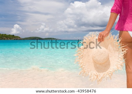 woman holding casual hat on tropical beach relaxing in sun on vacation
