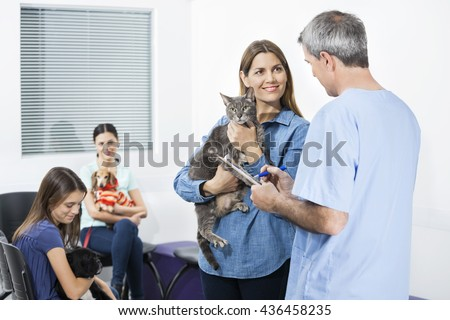 Woman Holding Cat While Looking At Nurse In Clinic - stock photo