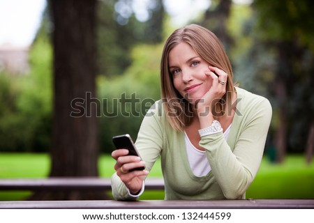 Woman holding Cell Phone in park. - stock photo