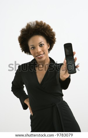 Woman holding cellphone out to view standing against white background.