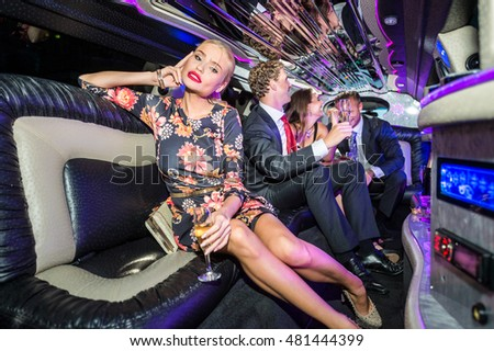 Woman Holding Champagne Flute With Friends Celebrating In Limousine