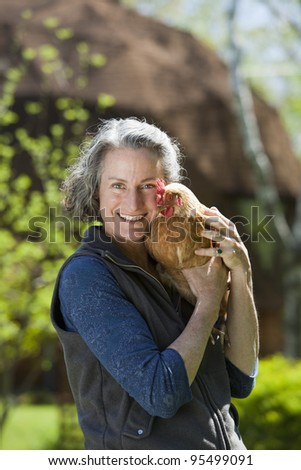 Woman holding chicken outside her geodesic home - stock photo