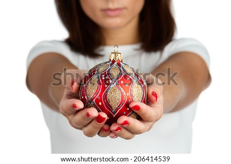 Woman holding christmas red ball, close-up of hands on white t-shirt background. - stock photo