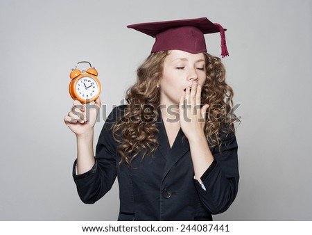 Woman holding clock in hands over grey background - stock photo
