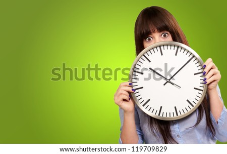 Woman Holding Clock Isolated On Green Background - stock photo