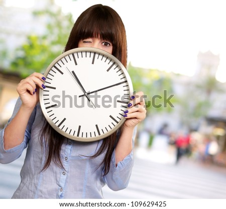 Woman Holding Clock Winking, Outdoor - stock photo