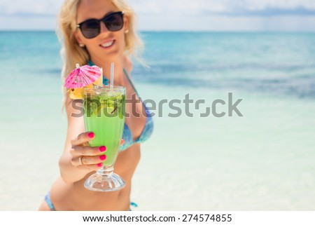 Woman holding cocktail on the beach