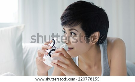 Woman holding coffee mug in bedroom, close up shot