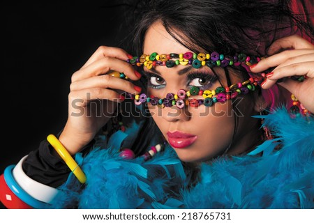 Woman holding colorful necklace of beads on his face. - stock photo